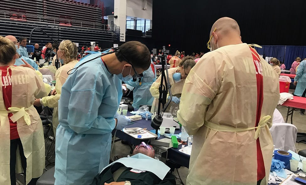 Dentists treating patients at community dental care event