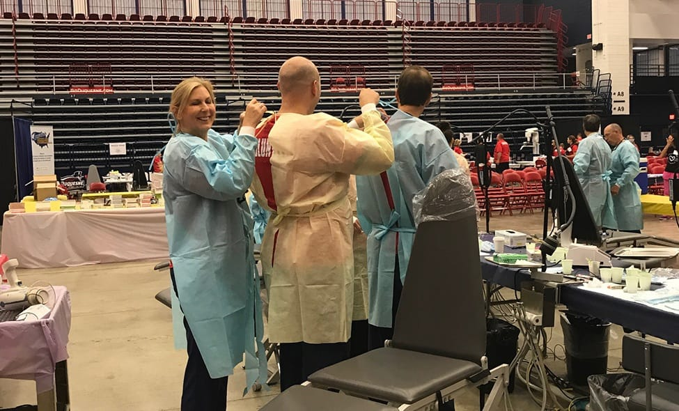 Dentists and team members putting on protective equipment at community event