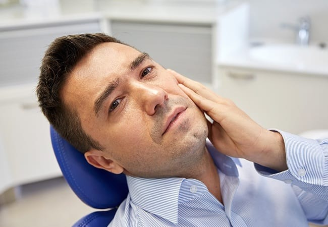 Man with a toothache holding his cheek at the dentist's office