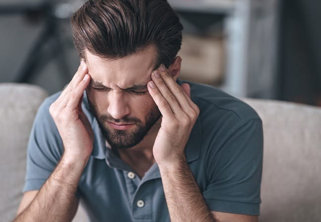 Man in need of T M J therapy holding head in pain