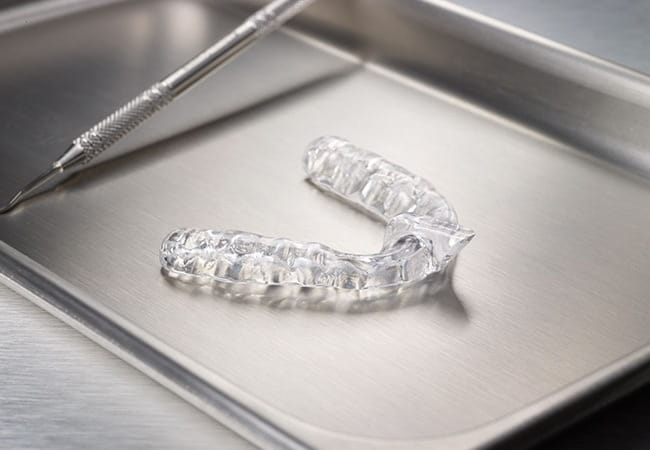 Clear plastic mouthguard on metal tray